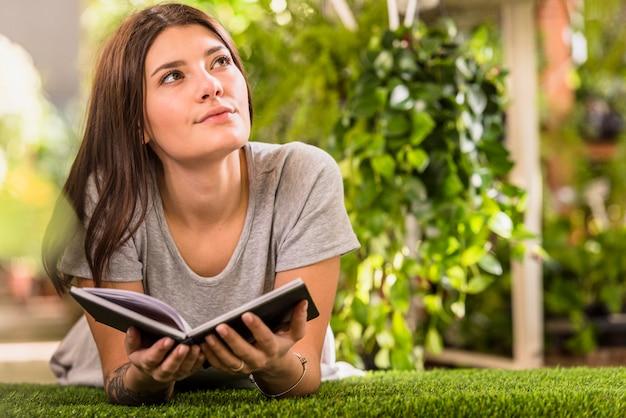Молодая задумчивая женщина с книгой, лежа на лужайке