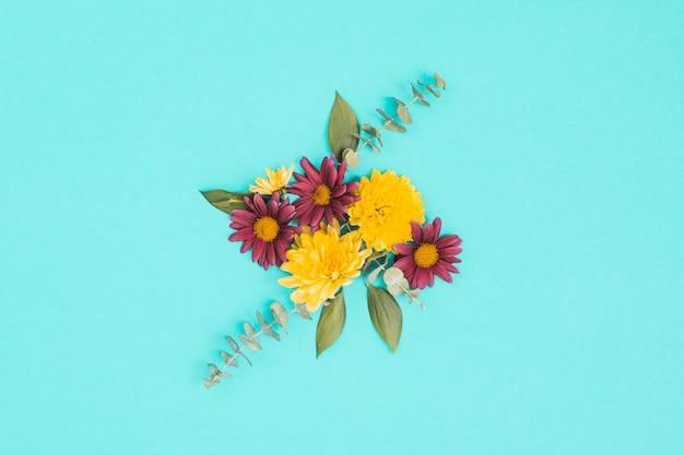 Разные цветы с зелеными листьями на столе