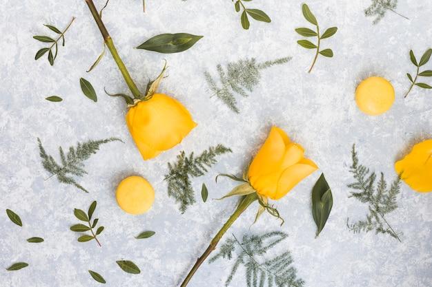 灰色のテーブルの上のマカロンとバラの花