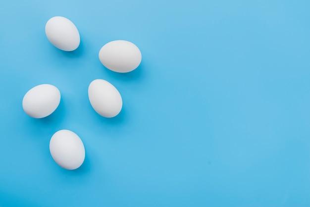 Набор белых яиц на синем фоне