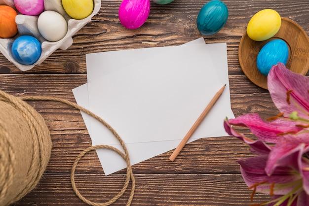 復活祭の卵、糸、新鮮な花のセット近くの論文