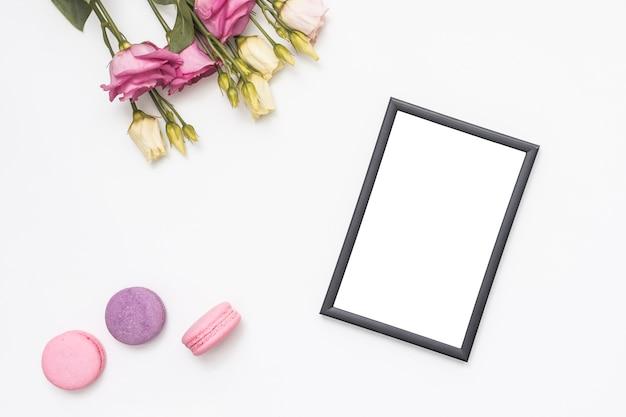 空白のフレームとマカロンのバラの花