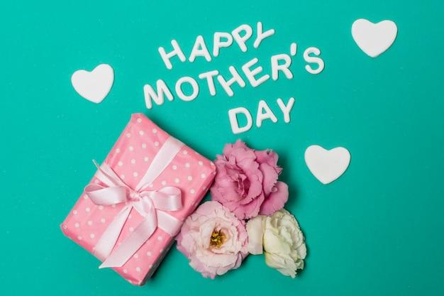 花とプレゼントボックスの近く幸せな母の日タイトル