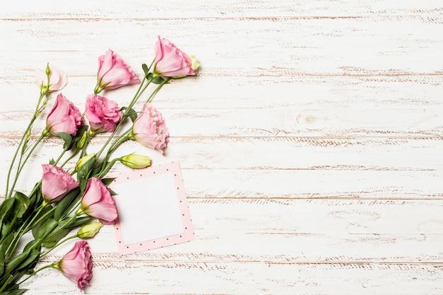 Свежие ароматные цветы возле бумажной рамки