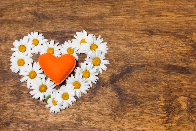 白い花とオレンジ色のおもちゃの装飾的な心