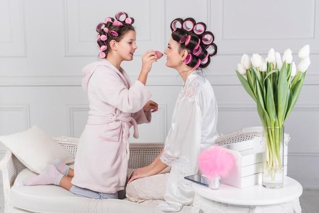 Симпатичная дочь наносит пудру на лицо матери