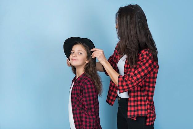 母娘の頭に帽子をかぶる