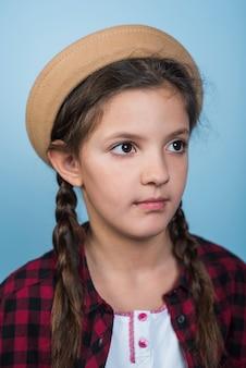 Вдумчивая девушка в шляпе с косичками