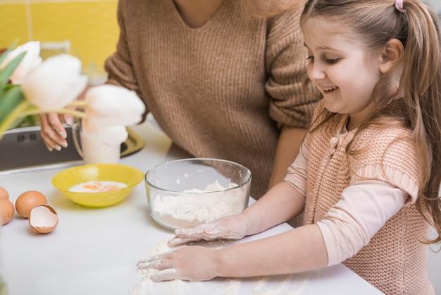 Мать и милая дочь, приготовление пищи на кухне