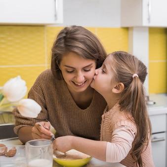 Милая дочь целует мать во время приготовления пищи на кухне