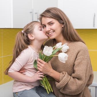 チューリップと母親の頬にキスを持つ少女