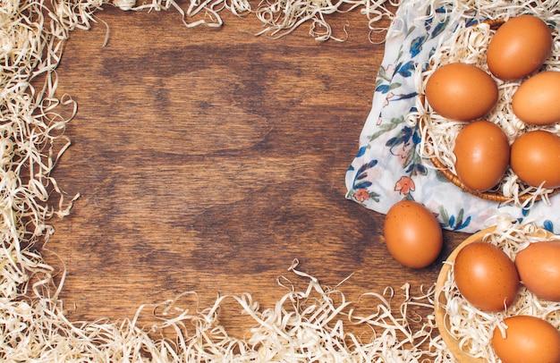 Куриные яйца в мисках на цветущем материале между мишурой на борту