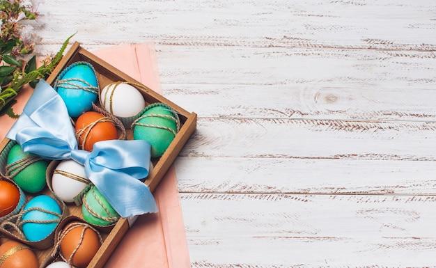 Коллекция ярких яиц в коробке на розовой крафт-бумаге возле растений