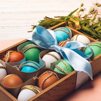 Яркие яйца в коробке возле букета цветов