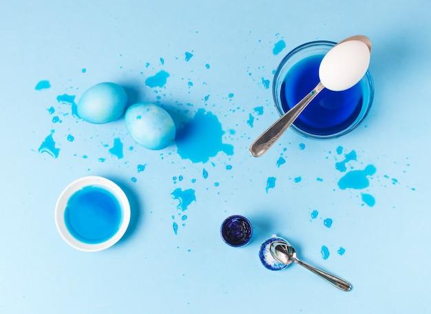 しみ、スプーン、染料の液体の間の青いイースターエッグのセット