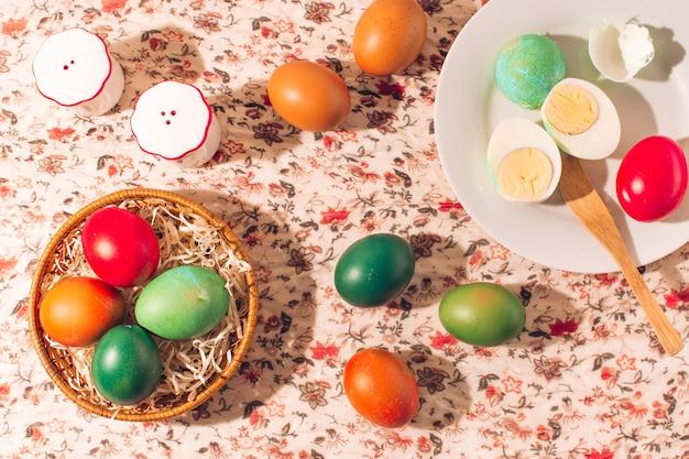 Пасхальные яйца на тарелках возле банки с солью и перцем