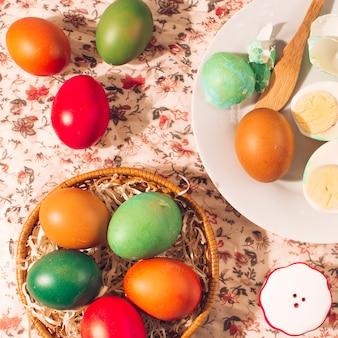 Яркие пасхальные яйца на тарелках возле соляной банки