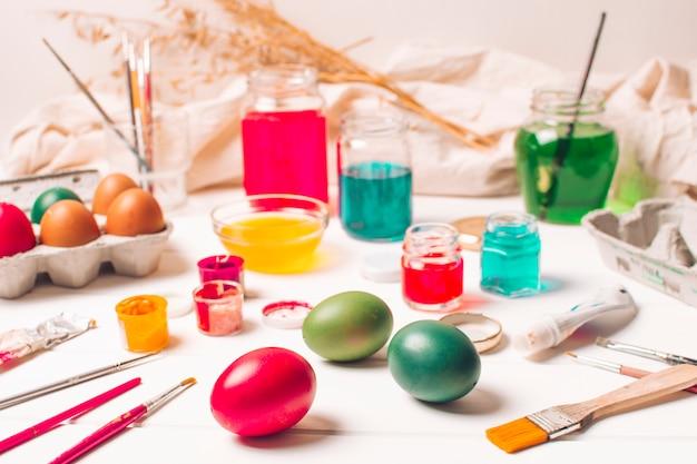 Яркие пасхальные яйца в контейнерах возле кисточек и краситель в банках