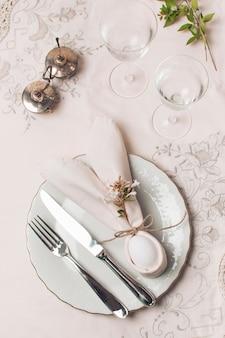 Салфетка и столовые приборы на тарелке возле стаканов и растений