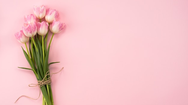 ピンクのテーブルの上の大きなチューリップの花の花束