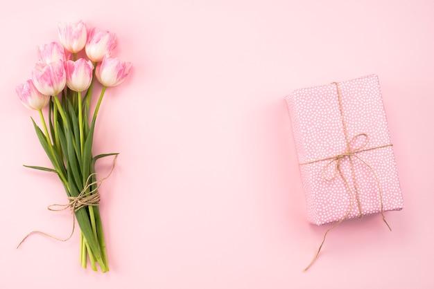 ピンクのテーブルの上のギフトボックスとチューリップの花束