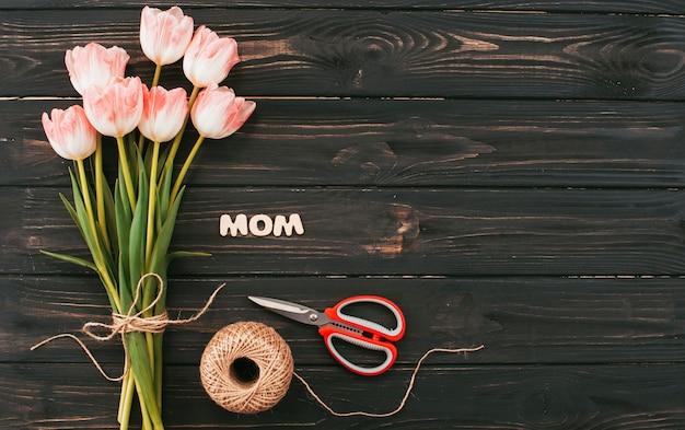 暗いテーブルの上のチューリップ花束とママの碑文