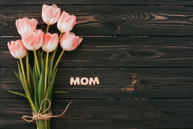 テーブルの上のチューリップ花束とママの碑文