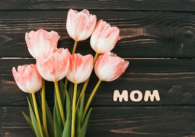 木製のテーブルの上のチューリップ花束とお母さんの碑文