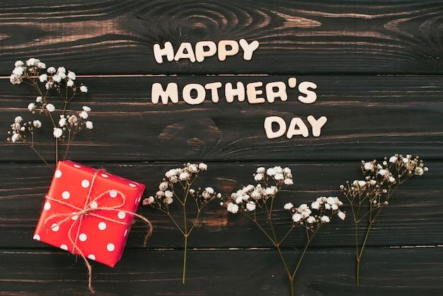 ギフト用の箱と花の枝を持つ幸せな母の日碑文