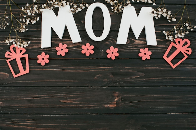 Мама надпись с цветочными ветками и подарками на столе