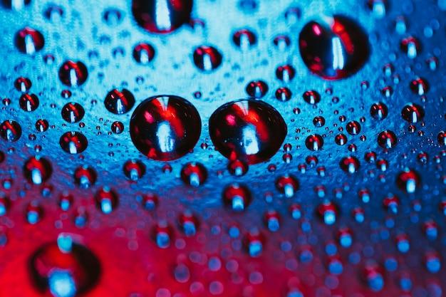 Структура капли воды на красном и синем фоне поверхности