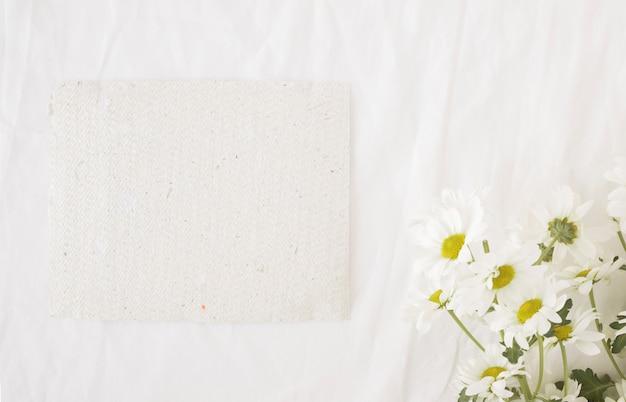 再生紙の近くの緑の茎の美しい花の束