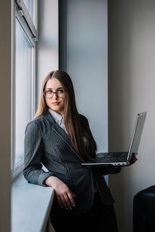 ノートパソコンを持つウィンドウに立っているスーツのビジネスウーマン
