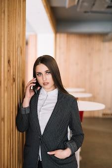 Молодой бизнес женщина разговаривает по телефону на стене