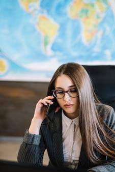 Деловая женщина разговаривает по телефону, сидя в офисе