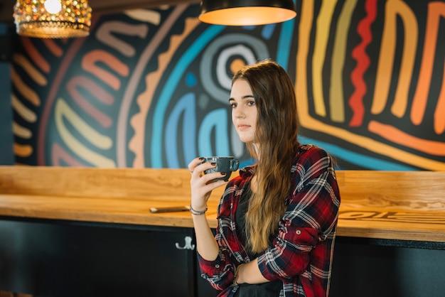コーヒーカップとカフェに座っている女性