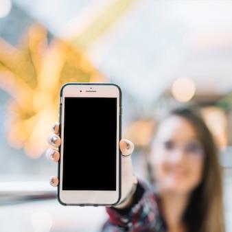 空白の画面を持つスマートフォンを手で保持している女性