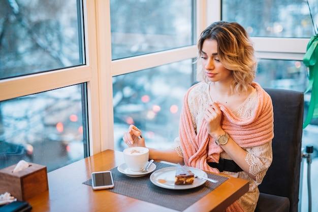 デザートとカフェのテーブルでスマートフォンの近くの飲み物のカップを持つエレガントな若い女性