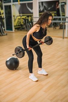 運動の若い女性がジムでバーベルトレーニング