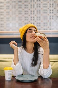 カフェのテーブルでカップ近くのデザートを持つ若い陽気な女性