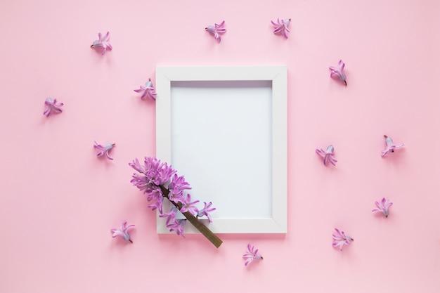 テーブルの上の空白のフレームと紫色の花支店