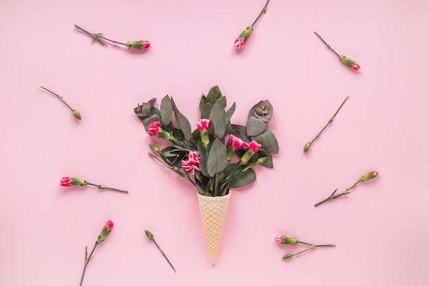 テーブルの上のワッフルコーンのピンクの花