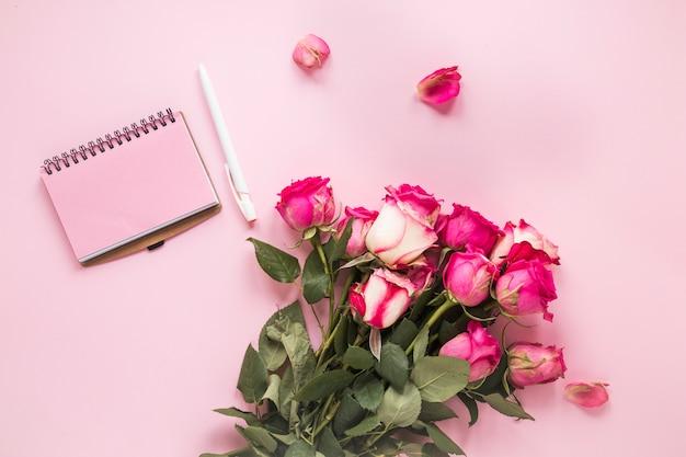 テーブルの上のノートとピンクのバラの花