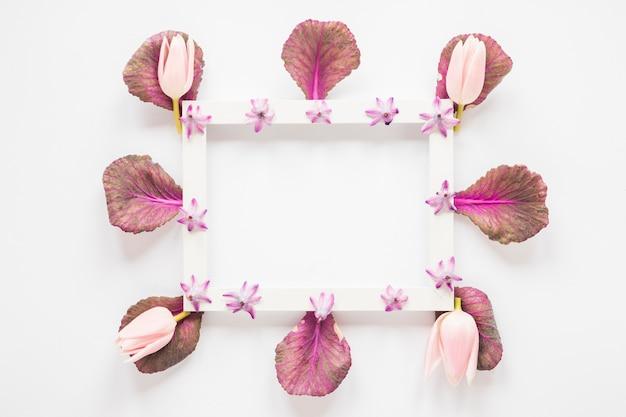 Пустая рамка с тюльпанами и листьями на столе