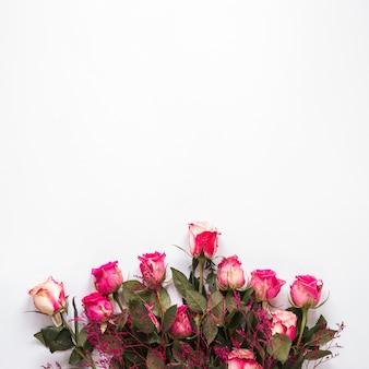 白いテーブルの上のピンクのバラの花