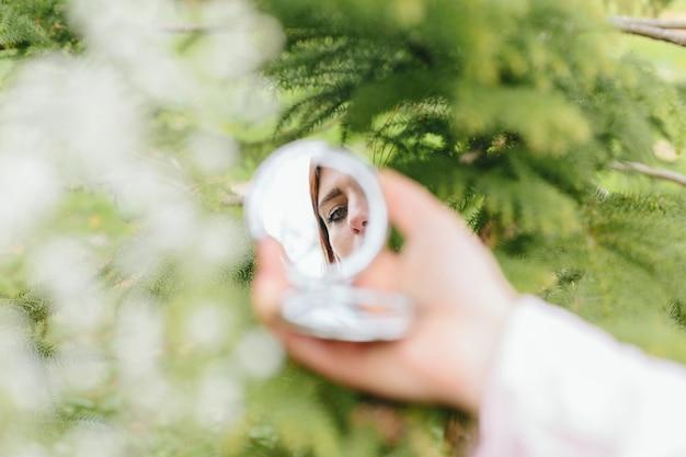 手の鏡の中の女性の反射