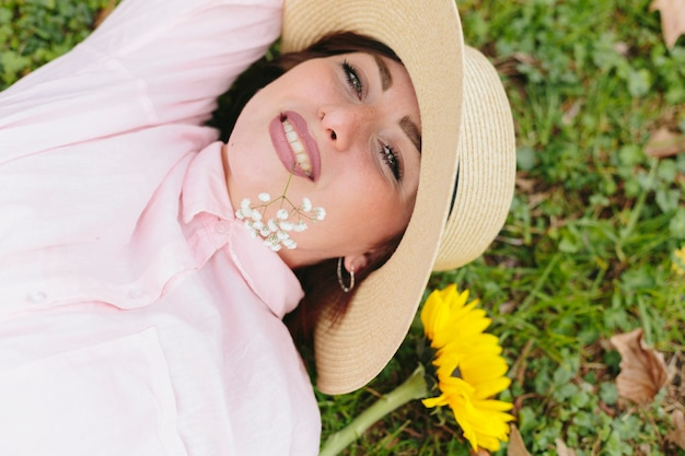 笑みを浮かべて、草の上に横たわる帽子の若い女