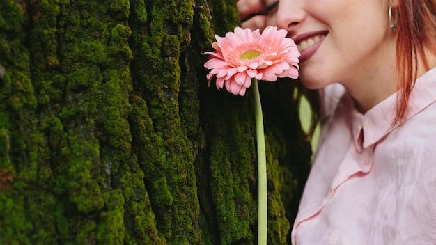 木の近くの花を持つ女性の笑みを浮かべてください。