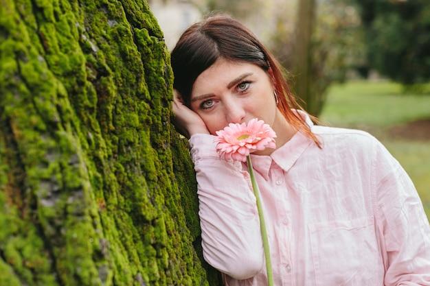 公園の木にもたれて顔の近くの花を持つ女性