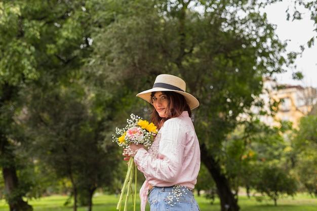 公園の花の束を持つ女性の笑みを浮かべてください。